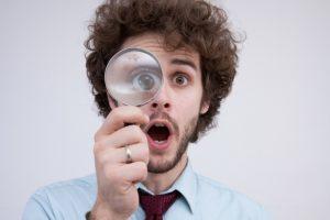 虫眼鏡をのぞく外人男性の画像