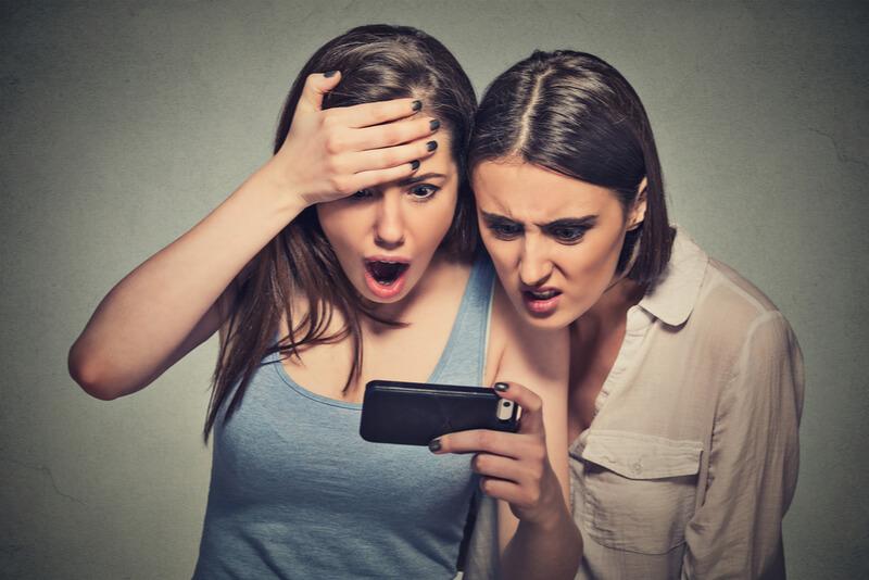 スマホを見て驚く2人の女性