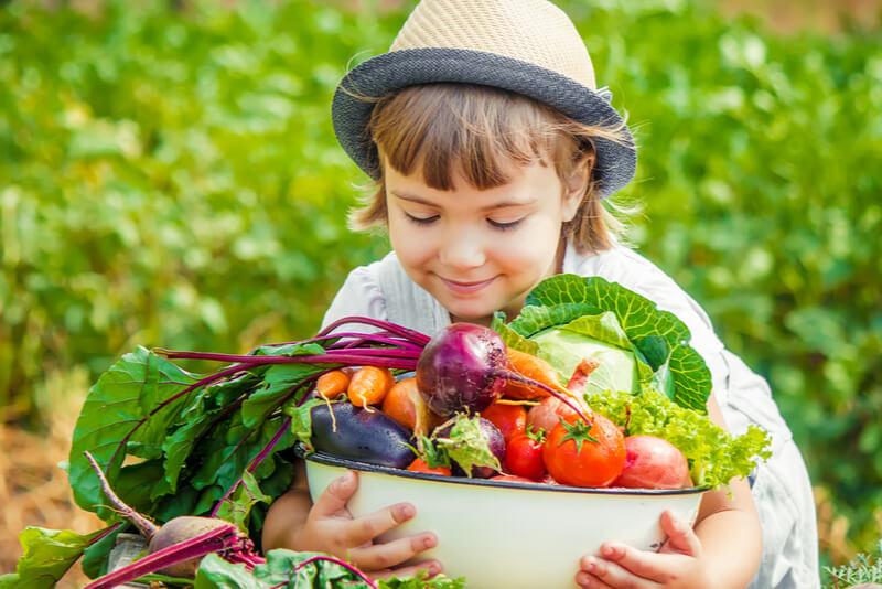 新鮮な野菜をもつ子ども